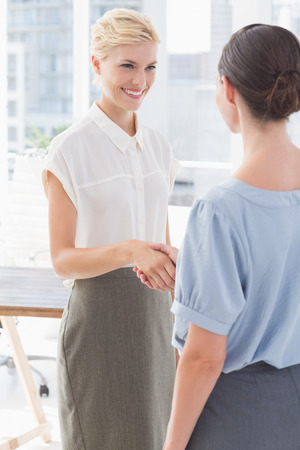 shaking hands: Businesswomen shaking hands in an office