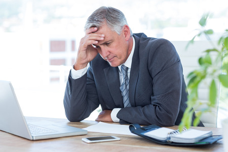 nervous: Worried businessman with head in one hand in his office