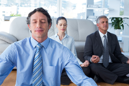 meditating: Business people practicing yoga in living room