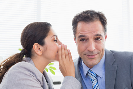 businessman smiling: Businesswoman whispering something to her colleague in an office