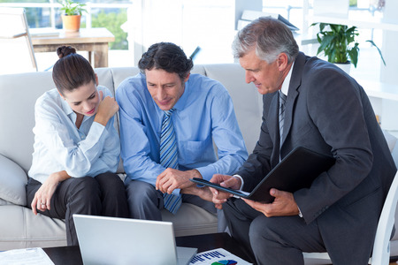 client: Couple in meeting with a financial adviser in living room