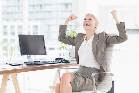 great success: Businesswoman celebrating a great success in her office