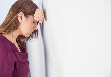 Depressed woman leaning her head against a wall on white background Stockfoto