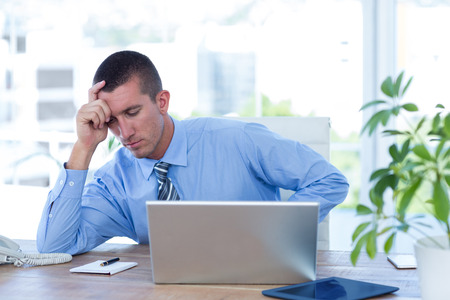 one hand: Worried businessman with head in one hand in his office