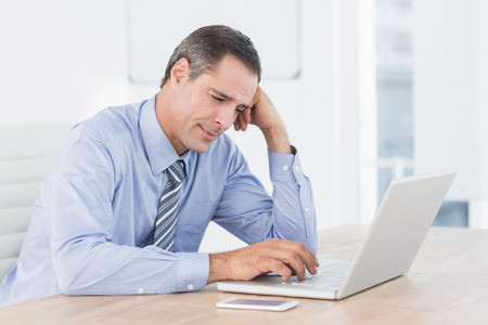 businessman working at his computer: Frustrated businessman working with his computer in his office