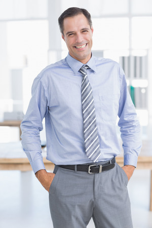 hands on pocket: Businessman smiling at camera with hands on his pocket in his office Stock Photo