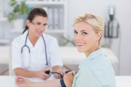 Arts die de bloeddruk van haar lachende patiënt in het medische kantoor