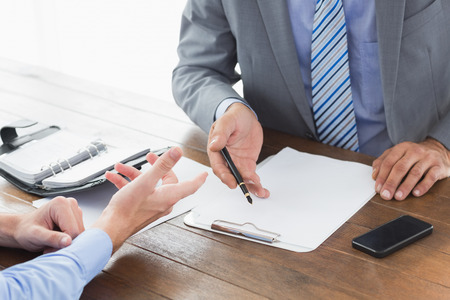 co: Businessman explaining contract to co worker in an office