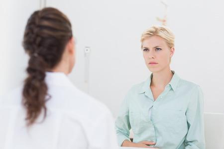 desolaci�n: habla paciente infeliz con el m�dico en el consultorio m�dico Foto de archivo