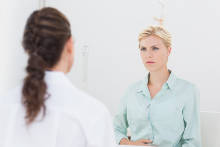 woman doctor: Unhappy patient speaking with doctor in medical office
