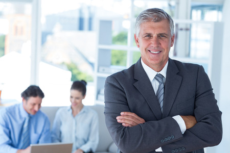 mature business man: Smiling businessman with arms crossed at office Stock Photo
