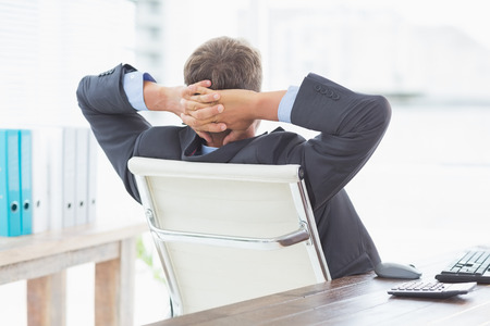swivel: Businessman relaxing in a swivel chair leaning back in his office