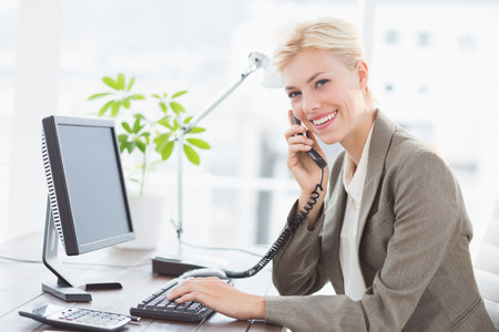 Businesswoman on the phone and using her computer in her office