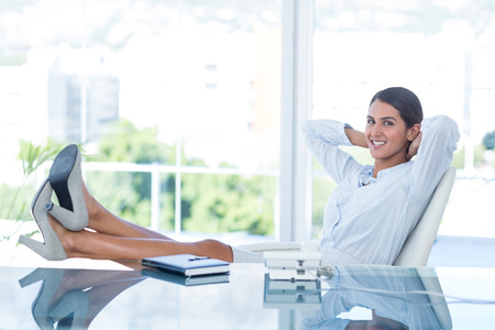 swivel chair: Smiling businesswoman relaxing in a swivel chair in her office Stock Photo