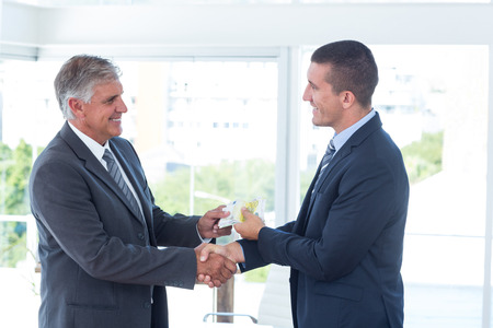 exchanging: Businessmen shaking hands and exchanging money in an office