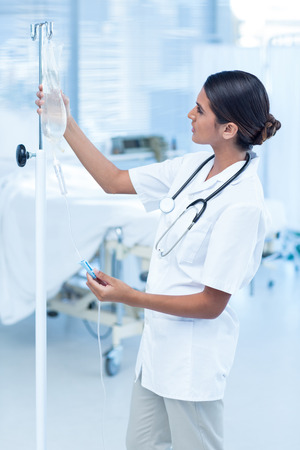 Hospital care: Nurse connecting an intravenous drip in hospital room