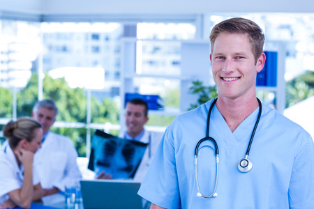mature male: Nurse smiling at the camera during a meeting