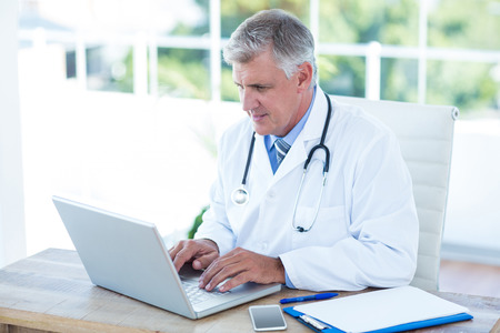 Serious doctor working on laptop at his desk in medical office