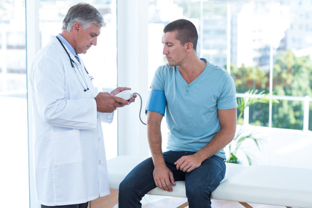 blood test: Doctor examining his patients blood pressure in medical office