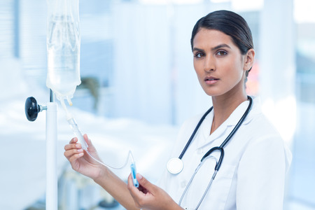 intravenous: Nurse connecting an intravenous drip in hospital room