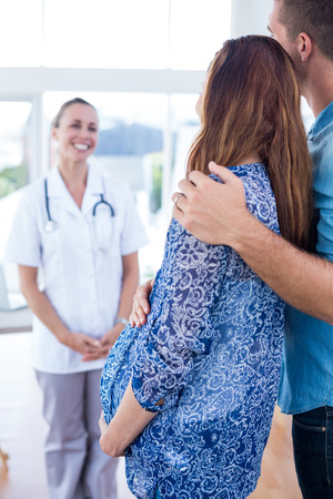 obstetrician: Smiling obstetrician and happy couple in medical office