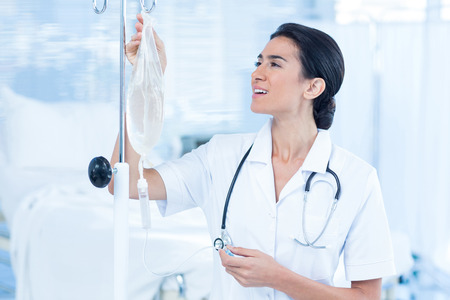 Nurse connecting an intravenous drip in hospital room Stock Photo - 42577986