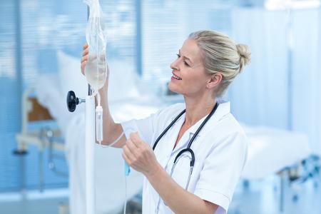 看護師が病室で点滴を接続します。 写真素材