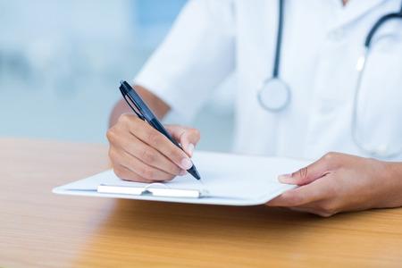 the clipboard: Doctor celebración portapapeles con archivo en la habitación del hospital