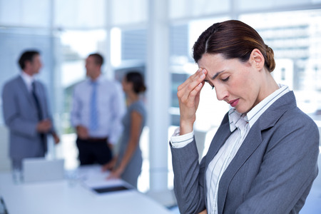 one hand: Worried businesswoman with head in one hand in an office Stock Photo