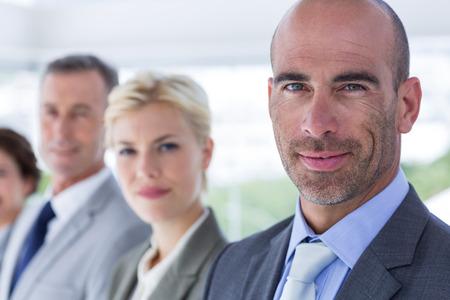 personas mirando: Business people looking at camera in the office Foto de archivo