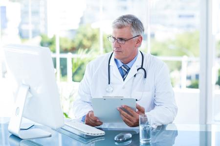 tecnología informatica: Doctor serio trabajo en la computadora en su escritorio en la oficina médica