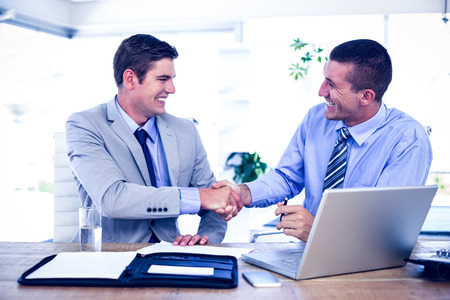 businessmen shaking hands: Businessmen shaking hands at desk in the office