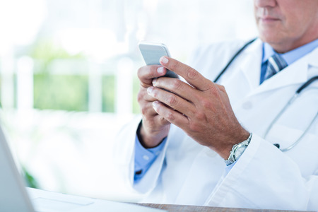 text message: Doctor sitting at his desk and texting in medical office Stock Photo