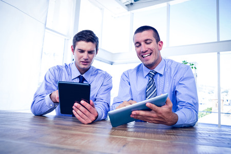 happy business team: Businessmen using their tablets in the office