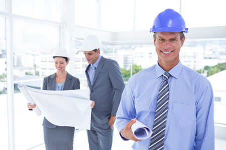 hard hats: Businessmen and a woman with hard hats and holding blueprint in the office