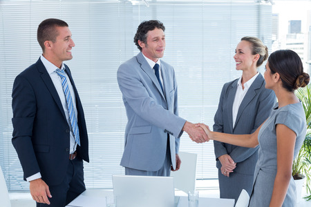 working attire: Business colleagues shaking hands in the office Stock Photo