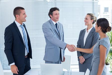 reuniones empresariales: Colegas de negocios d�ndose la mano en la oficina