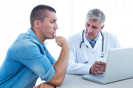 young adult men: Worried patient with his doctor in medical office Stock Photo