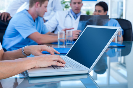 team from behind: Doctor typing on keyboard with her team behind in medical office