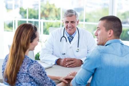 mid adult couples: Smiling doctor looking at happy couple in medical office