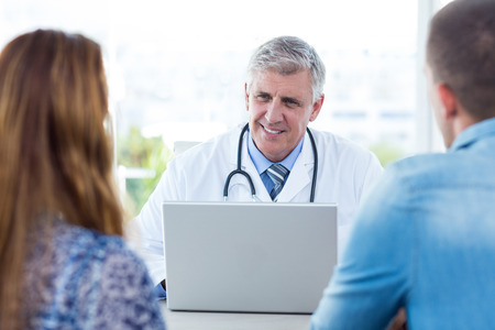 Smiling doctor talking to happy couple in medical office Stock Photo