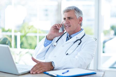uniformes de oficina: Doctor sonriente teniendo llamada de teléfono en su escritorio en la oficina médica