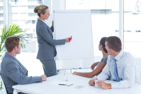 board room: Manager presenting whiteboard to his colleagues in the office Stock Photo