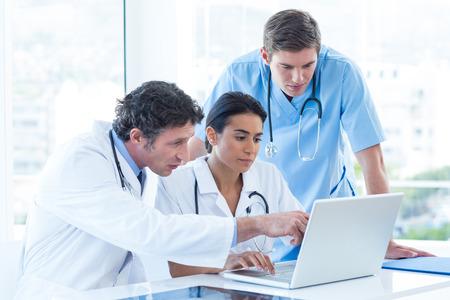 enfermeros: Equipo de médicos que trabajan en la computadora portátil en la oficina médica