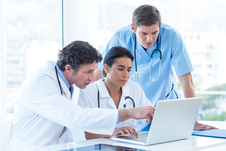 nurse computer: Team of doctors working on laptop in medical office