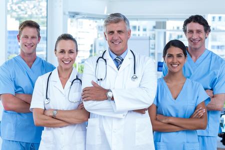 Team van artsen staan armen gekruist en lachend naar de camera in medische kantoor