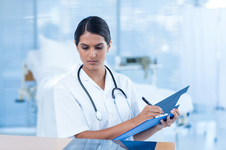 hospital notes: Beautiful doctor analyzing xray and taking notes in hospital room Stock Photo