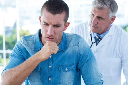 coughing: Doctor auscultating his patients back in medical office Stock Photo