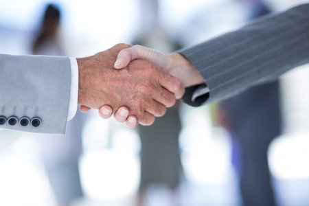 オフィスで同僚と握手するビジネスマン