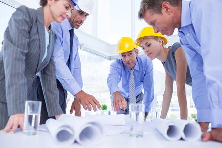 personas mirando: Personas de los hombres de negocios que buscan en el plan de construcci�n en la oficina Foto de archivo